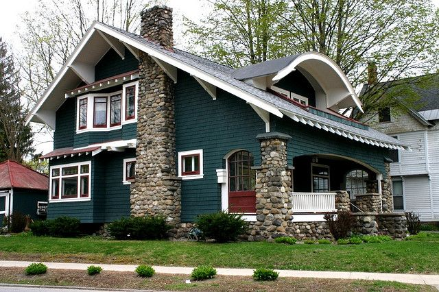 dark green + round stone piers on craftsman style bungalow porch