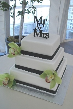 Simple square wedding cake with apple green orchids and a 'Mr. & Mrs.' cake topper.