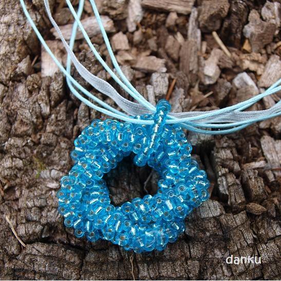 Tyrkysový uzlík šitý uzel tvoří hlavní motiv tohoto náhrdelníku. Délka stuhy je 45 cm + prodlužovací řetízek 5 cm.