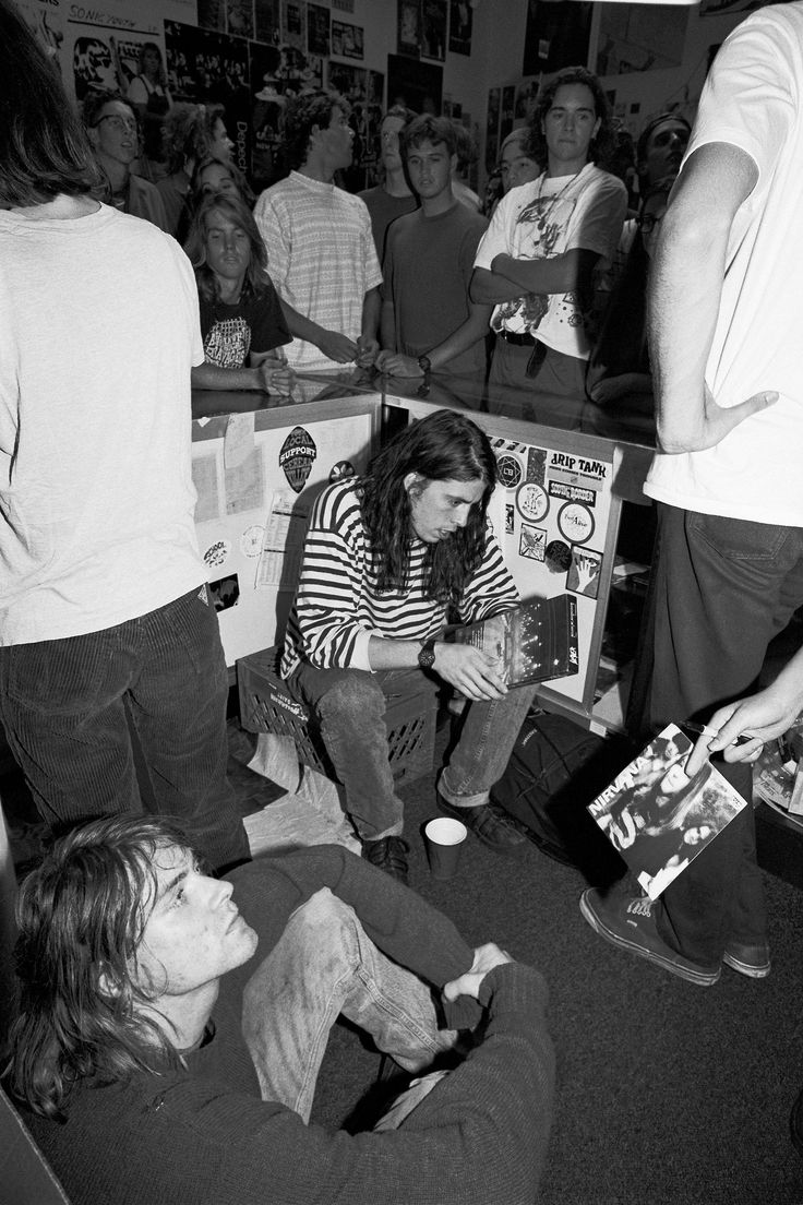 """Nirvana signing merch for Nirvana fans, 1991. Dave holding Slayer's """"Decade of Aggression"""" while Kurt listens to a fan giving him Nirvana's first single, """"Love Buzz."""""""