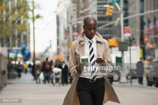 Stock Photo : Black businessman using cell phone on city street
