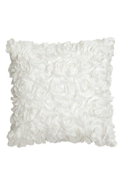 Housse de coussin en satin avec fleurs décoratives en mousseline. Fermeture à glissière dissimulée à la base.