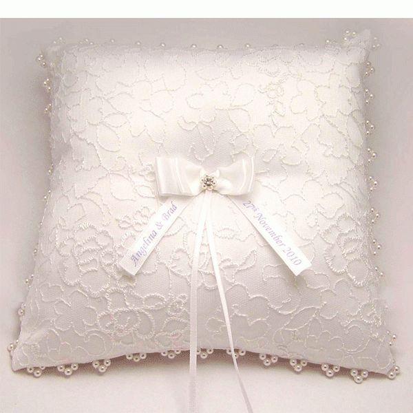 Белая кружевная подушечка, украшенная бантом с именами новобрачных, смотрится очень стильно.