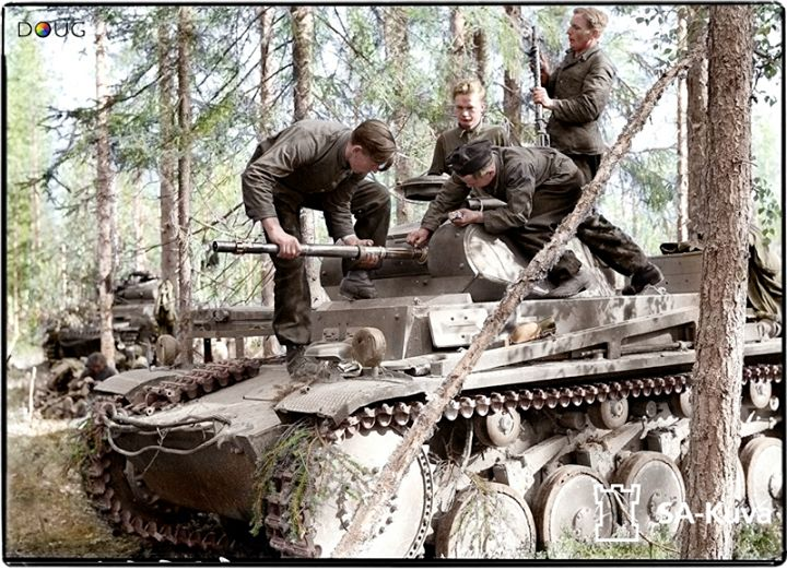 A Panzer II crew removing or replacing the small calibre barrel for cleaning purposes. This is the Panzer-Abteilung z.b.V.40 unit in Raatevaara, Finland. 27th June 1941. (Colourised by Doug)