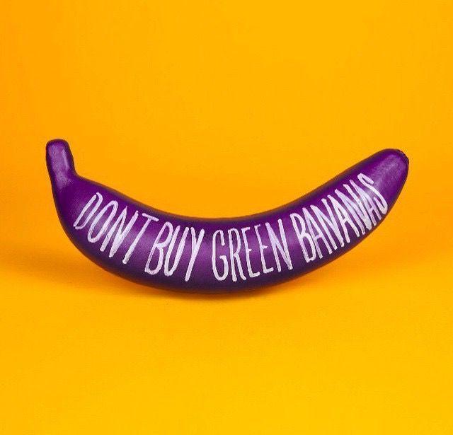 gele achtergrond, paarse banaan , surealistisch, witte tekst er op