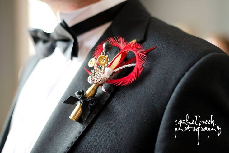 Bespoke handcrafted unique button hole from Lilly Dilly's in a bullet casing #james bond #wedding #theme #red #black #bullet #feathers #button hole