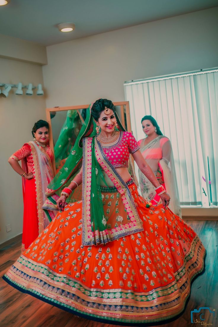 Twirling Brides - Orange, Green and Pink Lehenga | WedMeGood | Twirling Bride in a Orange Light Lehenga with a Pink Blouse and a Green Net Dupatta  Picture Courtesy: U Like Fotographia #wedmegood #twirling #lehenga