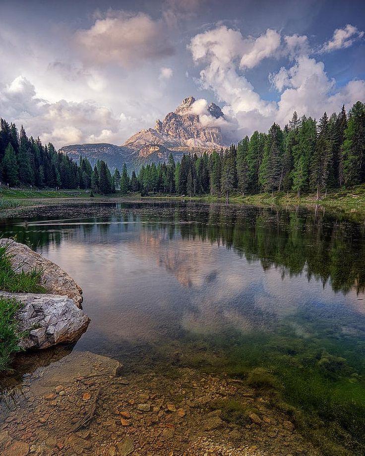 Le Tre Cime di Lavaredo circondate da nuvole  che bucano lo schermo si specchiano nelle acqua del lago di Antorno - Veneto Dolomiti