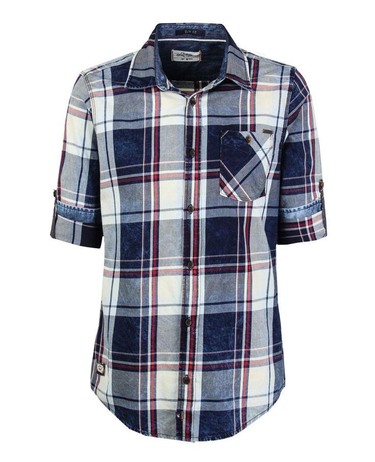 Camisa de hombre, con cuello y perilla completa de botones, manga larga. Preteñida a cuadros. Bolsillos de parche con botón y placa metálica en el frente. Composición Prenda: 100% Algodón.