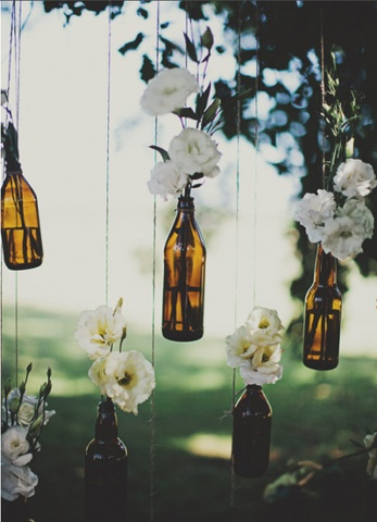 Empty beer bottles with white flowers in it hanging from a tree