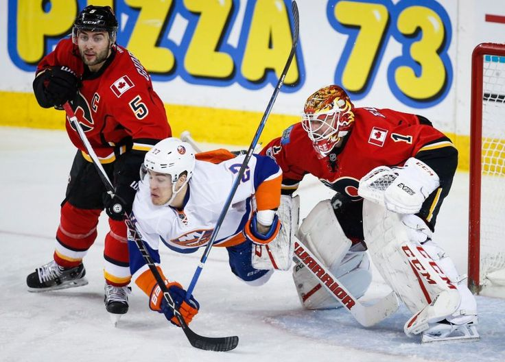 Islanders vs. Flames:     March 5, 2017  -   The Islanders fell to the Calgary Flames, 5-2, on Sunday at the Scotiabank Saddledome.   -      New York Islanders' Anders Lee, centre, is knocked to the ice by Calgary Flames' Mark Giordano, left, as goalie Brian Elliott looks on during third period NHL hockey action in Calgary, Alberta, Sunday, March 5, 2017.