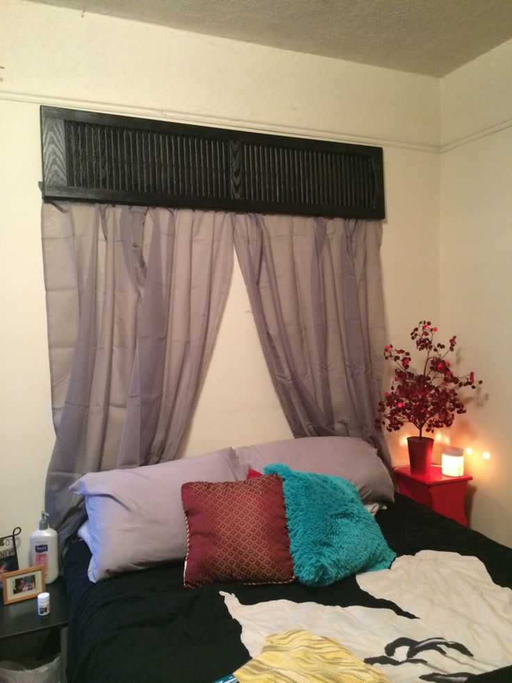 Above bed display. Repurposed plastic shutter, spray painted black, attached some grey, sheer panels. Romantic!