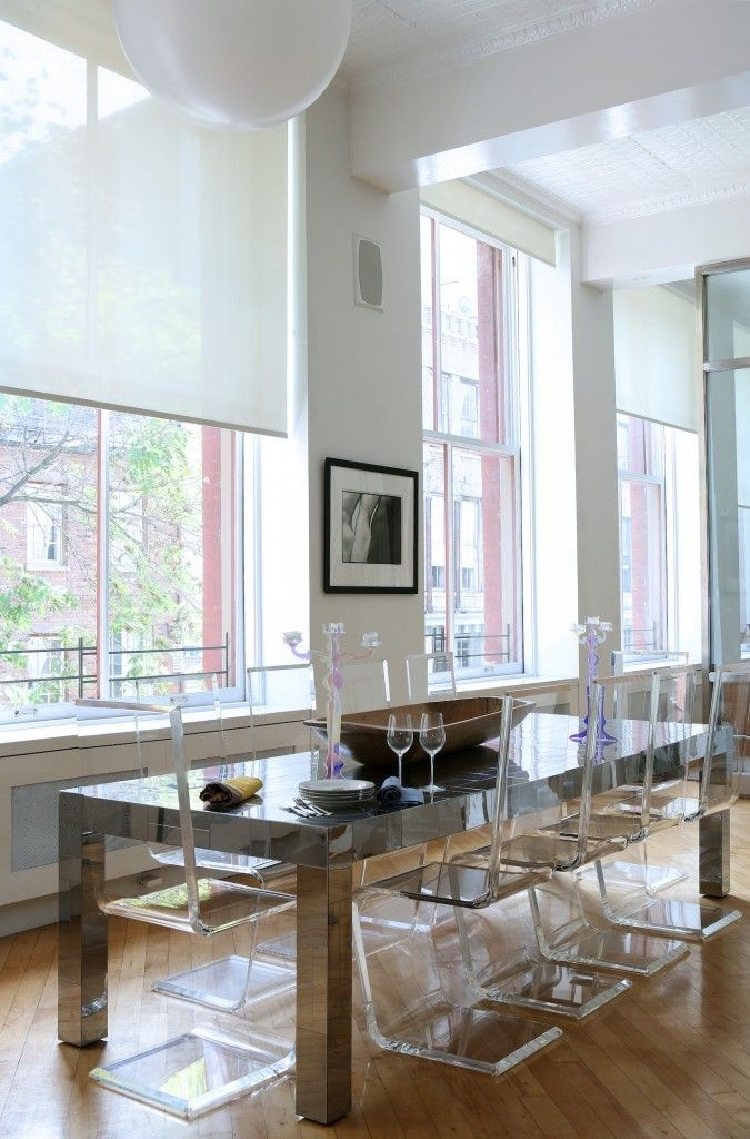 This contemporary dining room has smooth one-line transparent chairs and a metallic dining table. The seamless windows reach up to the top of the high ceilings and have Roman shades for privacy.
