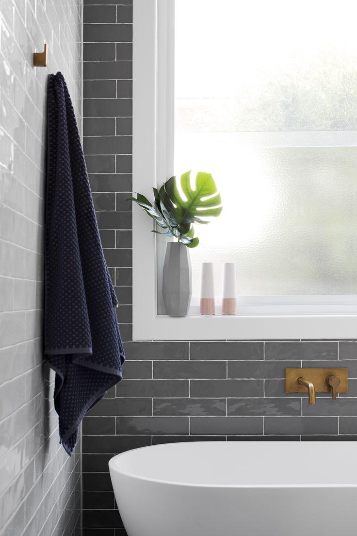Gray subway tiling behind white bathtub