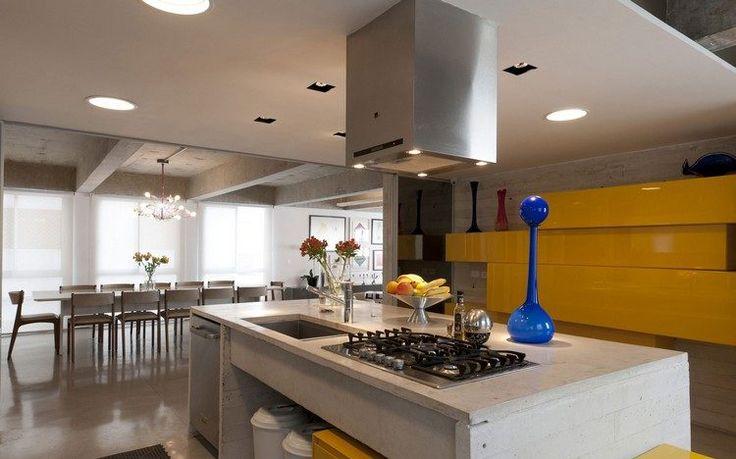 cuisine moderne en béton et jaune laqué, sol en béton ciré, table à manger en bois et chaises assorties