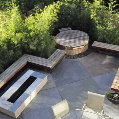 Modern Patio Design with wood bench seating and matching hot tub cover/surround that blends into the patio. Diagonal cement squares; great complement