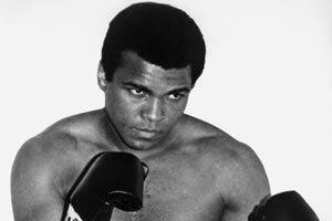 """Eleito pela renomada revista esportiva Sports Illustrated, em 1999, como o """"Desportista do Século"""", o americano Muhammad Ali ganhou uma medalha de ouro nos Jogos Olímpicos de Roma, em 1960, e tem em seu nome o incrível cartel de 57 vitórias e somente 5 derrotas na carreira. Encerrou sua carreira em 1981, quando ainda era Campeão Mundial dos Pesos-Pesados."""