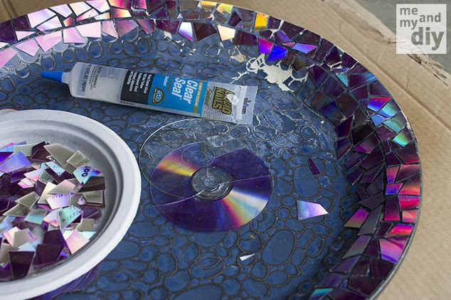 mosaic tile birdbath using recycled dvds, crafts, gardening, repurposing upcycling, After sealing the cut DVD pieces to protect the shiny layer I used a strong clear flexible adhesive to attach them to the top and edges of the birdbath