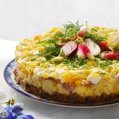 En ny variant på silltårta med matjessillens klassiska tillbehör. Kokt ägg, potatis, rödlök och brynt smör på en kavringsbotten.