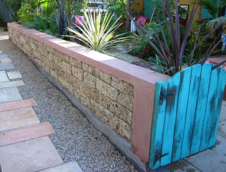 Urbanite walls, Lime wash, pigmented, painted walls and distressed wooden garden gate, complement the authentic Mexican feel of this garden.