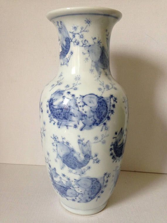 Very pretty Chinese ceramic vase with koi carp design.  With a crisp, white background and decorated with muted blue Koi fish swimming all around the body of the vase in a sea of bubbles. In China, carp are considered a symbol of strength. Koi carp are constantly swimming upstream against the current and it is because of this that their image is used to represent strength, independence, perseverance, ambition and good luck.  Hand painted in beautiful shades of blue.  Finished with a blue…