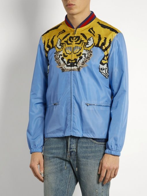 Gucci's sky-blue shell bomber jacket is made in Italy, and decorated with the new-season Bengal tiger motif – note how it cleverly runs the length of the back. The navy and red ribbed trims nod to the iconic Web stripe. Fits true to size. http://www.matchesfashion.com/products/Gucci-Tiger-print-shell-bomber-jacket--1076933