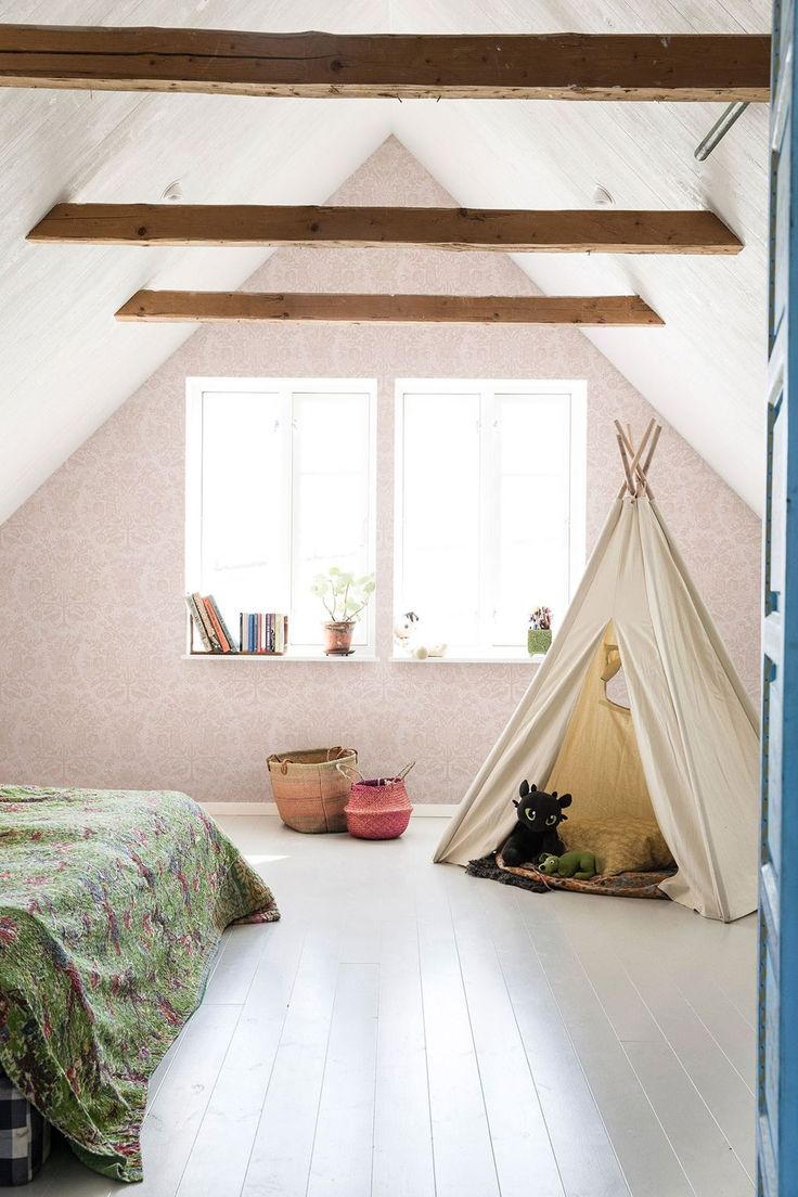 "This children's bedroom is in an airy attic space. The gable wall has been papered in [link url=""https://sandbergwallpaper.com/""]Sandberg's[/link] delicate 'Mika' wallpaper, highlighting the architectural shape of the apex. The wooden floorboards have been painted in a practical, wipe-clean gloss paint. A calico teepee is a fun den - for something similar try [link url=""http://www.hobbycraft.co.uk"