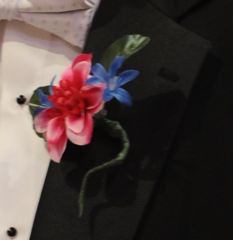 Boutonniere from our wedding.  Materials: Floral tape, floral wire, high-power magnets, artificial flowers (one large flower and two smaller), hot glue gun (and glue).  Cost: about $3 per boutonniere.  Again, I saved a lot on making these myself--the florist was charging twelve dollars per boutonniere for the cheapest flowers, which just wasn't going to happen.  These were a little tougher than the bouquets, but still doable.  Pick out one nice large flower and, if you want, two smaller…