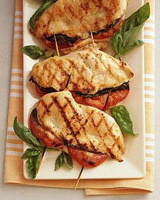 """Grilled Chicken Stuffed with Basil and Tomato.  Before grilling, soak the toothpicks or skewers in water for 30 minutes to prevent them from burning. Butterflying the chicken -- splitting each piece in half and fanning it open like a book -- creates two layers. They make tasty """"sandwiches"""" with tomato and basil."""