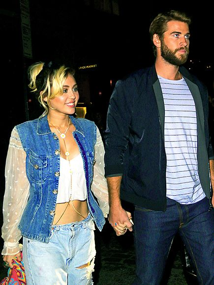 Miley Cyrus sports a tailored blue denim jacket with sheer, lace-trimmed sleeves while out to dinner with Liam Hemsworth in New York City, September 2016.