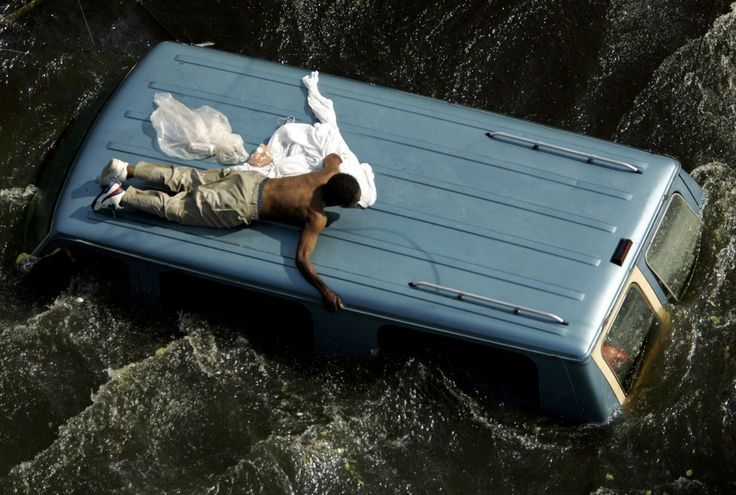 Sept. 4, 2005 — Hurricane Katrina (ph: Robert Galbraith / Reuters) A man clings to the top of a vehicle before being rescued by the U.S. Coast Guard from the flooded streets of New Orleans in the aftermath of Hurricane Katrina