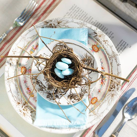 Three distinct floral patterns ring the edges of the dishes in this outdoor table place setting. When mixing different designs, use a single color to unite the setting. Here, the designs are brought together with a light blue napkin. A few faux bird eggs resting in a tiny nest (available at crafts stores) add nature to your outdoor party.