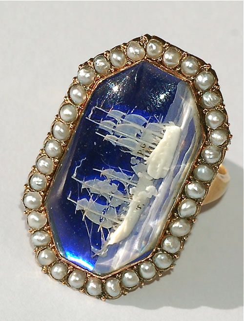High carat gold ring, circa 1798 -1800, containing a virtuoso micro-ivory carving of warships engaged in battle, with cannons blazing. The vessels are set on a cobalt blue glass ground, in an octagonal glazed compartment, within a seed pearl surround.