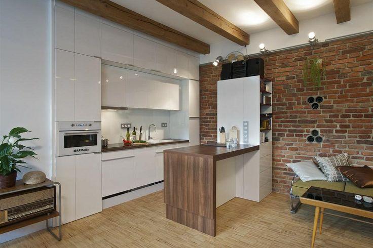 Moderní bílá kuchyň je vybavena všemi potřebnými spotřebiči včetně pračky a bojleru. Pracovní ostrůvek opticky odděluje kuchyň od zbytku bytu a je možné jej rozložit na jídelní stůl. Původní cihlová stěna zůstala zachována. Komínové cesty využil majitel jako minivinotéku.