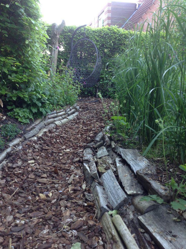 Pad van boomschors met daaronder worteldoek en afgesloten met houtblokken. Ook de verhogingen hebben we afgewerkt met kleine boomstammen en houtblokken.