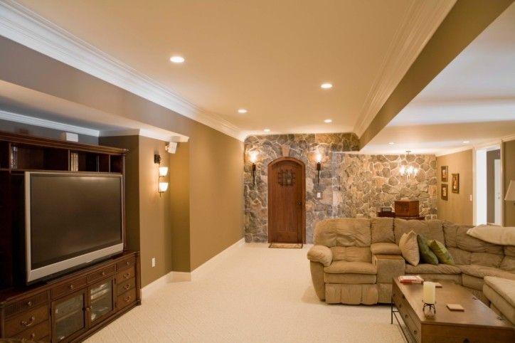 Große fertig Keller mit großen TV-Bildschirm, Schnittsofas, Felswand, Einbauleuchten, Beleuchtung