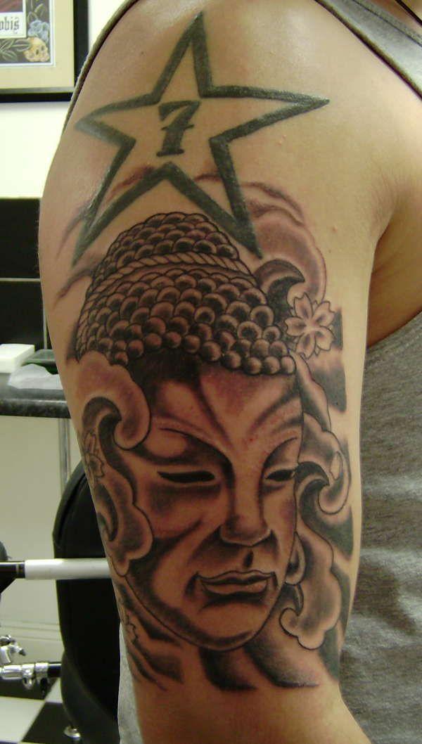 腕に星と仏の頭のタトゥー