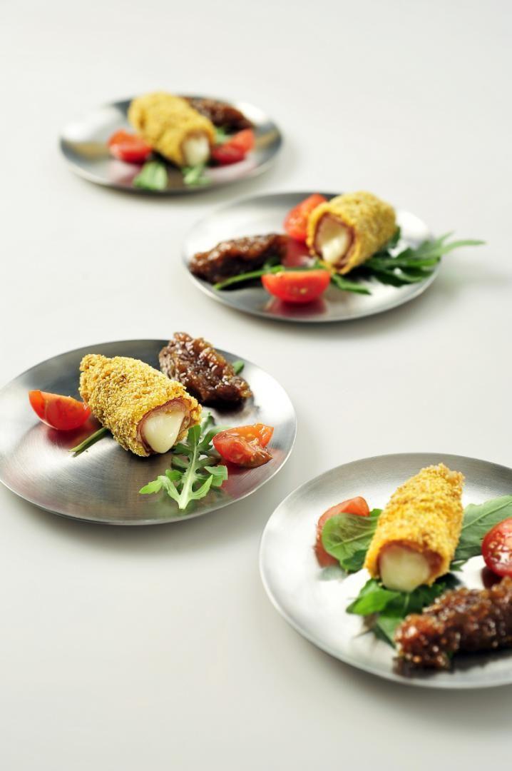 Bereiden:Leg de plakjes parmaham op het werkvlak en leg op iedere plak een stukje mozzarella.Maak er een stevig rolletje van.Haal de rolletjes eerst door de bloem, vervolgens door het eigeel en tenslotte door de polenta.Frituur de rolletjes gedurende 5 minuten op 160 graden en laat ze daarna uitlekken op keukenpapier.Werk af met partjes kerstomaat, blaadjes rucola of basilucum en serveer met vijgenconfituur.