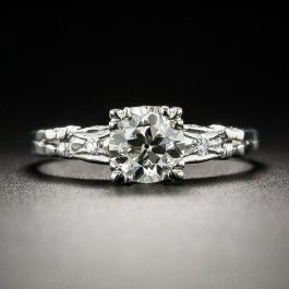 A beautiful, bright and brilliant European-cut diamond, weighing .78 carat, sizzles mostly solo between diamond-dotted shoulders in this traditional vintage sparkler, hand-fabricated in platinum, circa 1930. The scintillating stone is well secured by four trefoil prongs which add dimension to the diamond's outline. A timeless late-Art Deco classic. Currently ring size 5 3/4.