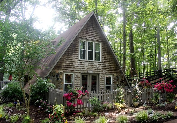A-Frame cottage with cedar clapboard siding in the woods. The inside is just as charming, with an amazing antique brick kitchen floor.