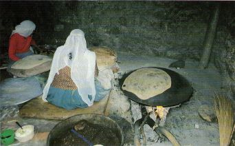 'n Bedoeienvrou is besig om brood te bak in 'n groot skottel wat oor die vuur gekeer is.  'n Bedoeienvrou is besig om brood te bak in 'n groot skottel wat oor die vuur gekeer is.