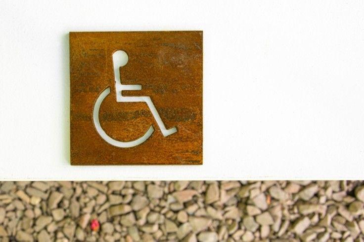 """Zdjęcie tabliczki """"wc niepełnosprawni"""" ze stali Corten ( zdjęcie wykonane po dwóch miesiącach patynowania )."""