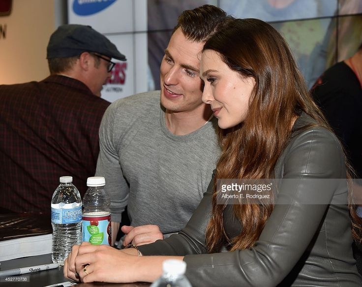 Actors Chris Evans (L) and Elizabeth Olsen attends Marvel's 'Avengers: Age Of Ultron' Hall H Panel Booth Signing during Comic-Con International 2014 at San Diego Convention Center on July 26, 2014 in San Diego, California.