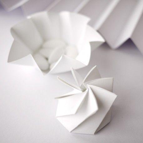 Véritable sculpture de papier, cette petite boîte est un pliage savant qui étonnera vos invités. Toute en plis qui se twistent et se détwistent, elle s'ouvre comme une fleur et se ferme comme un diaphragme. Du grand art. Petite contenance intérieure : 4 ou 5 dragées. Livrées pré-pliées, par nos soins longs et délicats. Création Serge Barbier. Modèle déposé.