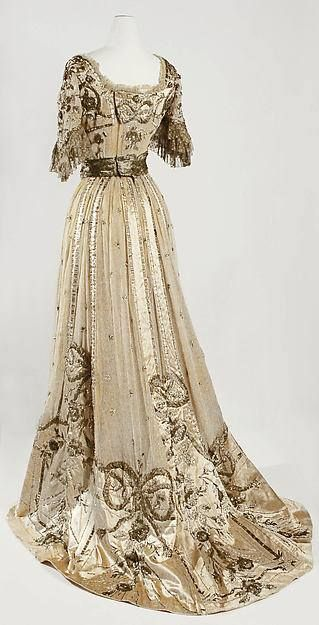 The sweeping back silhouette of this gown, the heavily beaded and appliquéd work and the elbow-length sleeves indicate a date of ca. 1907-09.