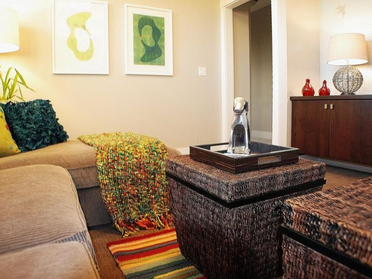 Living Room: Eclectic Living Room With Wicker Coffee Table. coffee table with storage. hamper coffee table. brown sofa. wooden chest. framed wall art. colorful rug. globe lamp base.