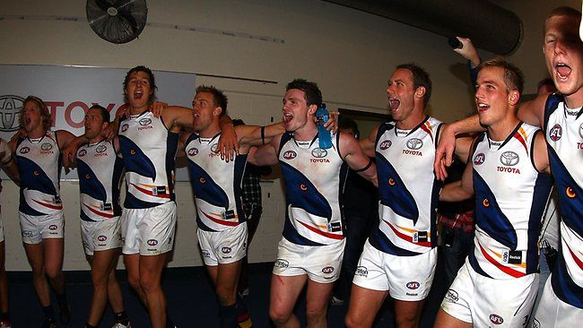 Adelaide Crows players sing their team song after beating Carlton at Etihad Stadium.