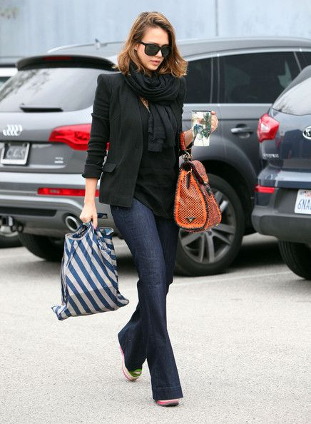 Jessica Alba in dark denim flares, platforms and black tee, jacket and scarf