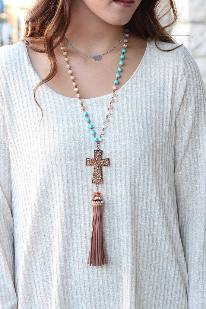 Long length tassel necklace featuring a copper bling cross and turquoise and crystal beads on the chain. We love this statement piece.