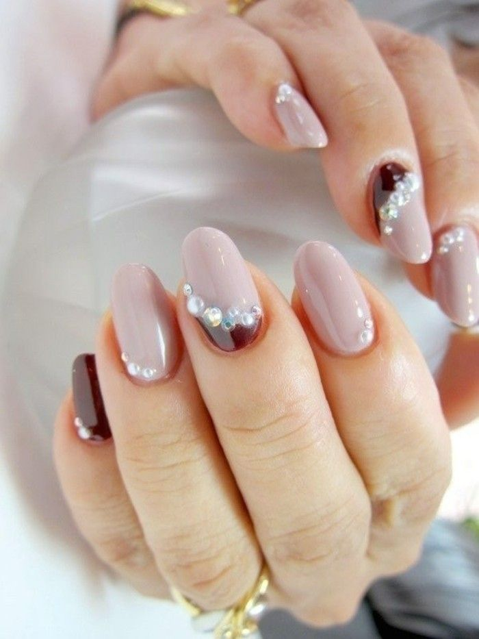 round nails colored in light and dark plum nail polish, decorated with silver rhinestones